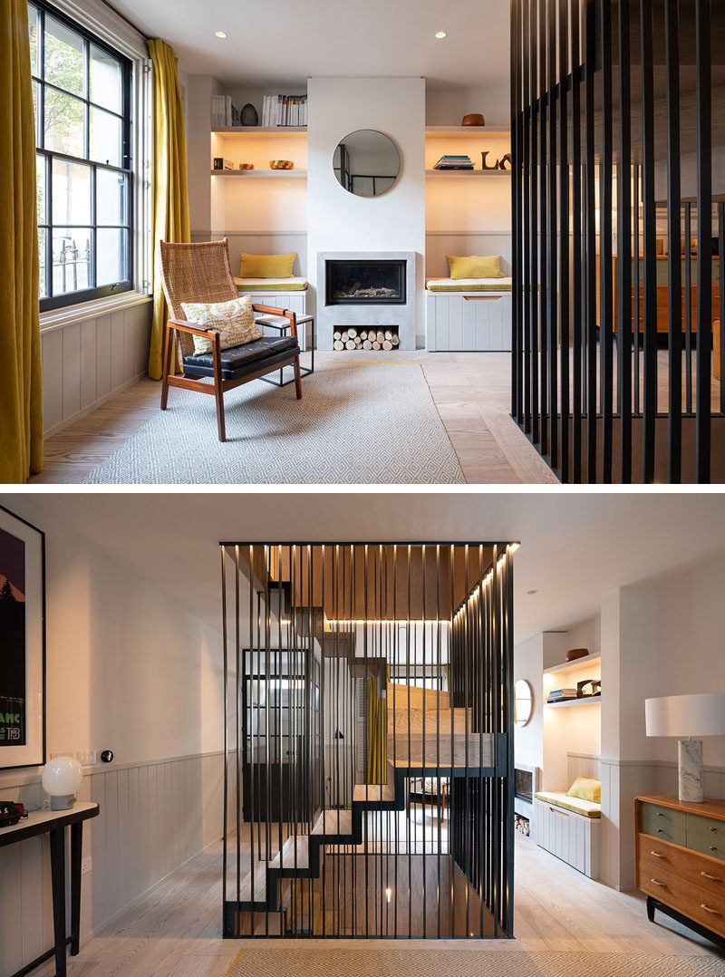 In this sitting room, built-in shelving with hidden lighting is located on both sides of the fireplace, while powder-coated metal work can be found framing the staircase. #SitttingRoom #Fireplace #Staircase