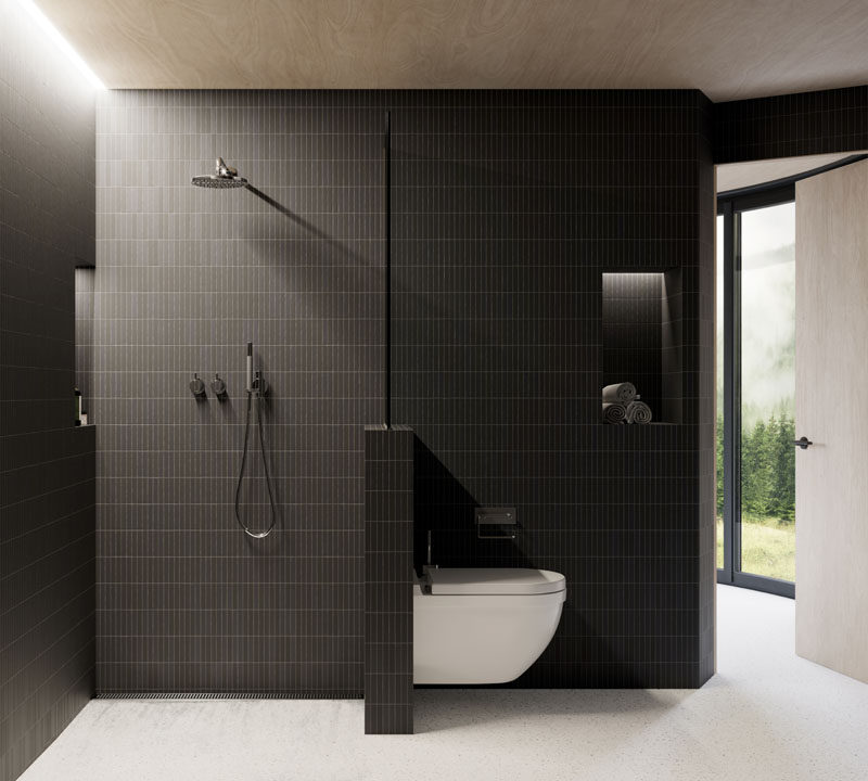This modern bathroom has dark tiles that contrast the wood ceiling, while hidden lighting helps to keep the small space bright. #ModernBathroom #BathroomDesign