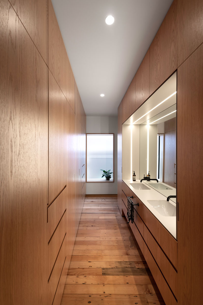 This modern master suite has a custom designed ensuite walk-through dressing room and bathroom vanity. #WoodCloset #WoodVanity