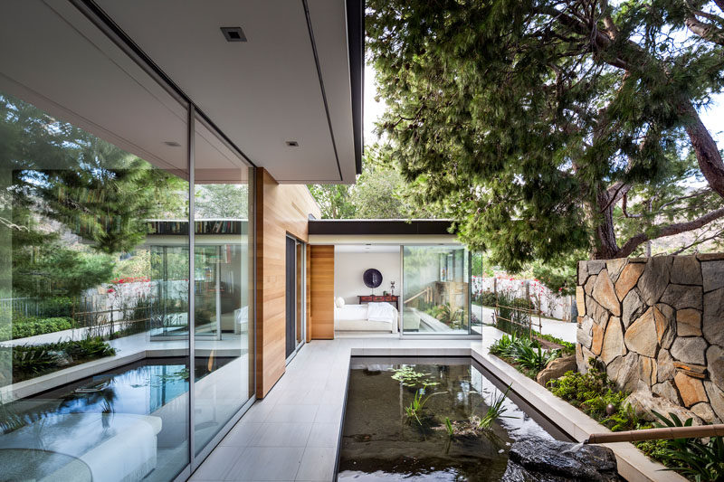 This modern house has a water feature that can be enjoyed from one of the bedrooms. #WaterFeature #ModernPond #LandscapeDesign #Landscaping