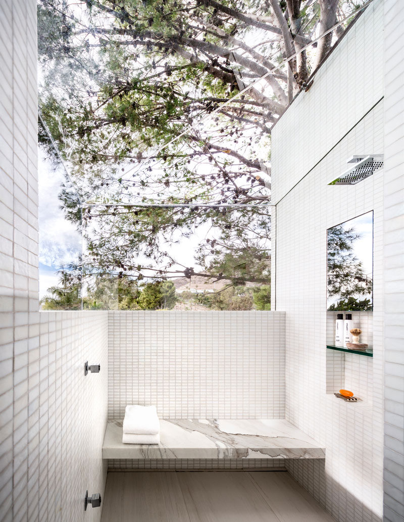 In this modern and white bathroom, a glass ceiling and partial wall in the shower provide uninterrupted views of the surrounding landscape. #ModernBathroom #Windows