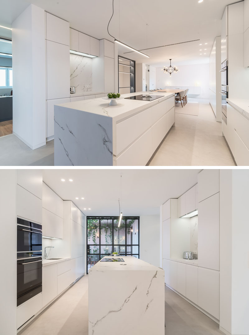 In this modern kitchen, minimalist white cabinets line the walls and a large island is centrally located. #ModernWhiteKitchen #ModernKitchen #WhiteKitchen