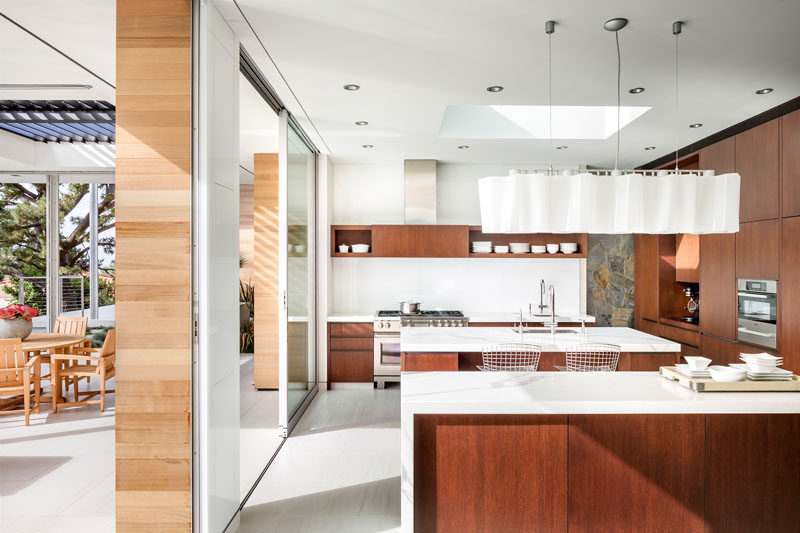 In this modern kitchen, marble countertops have been combined with stained rift white oak cabinetry, while two islands provide plenty of space for entertaining. #KitchenDesign #ModernKitchen #WoodAndWhiteKitchen