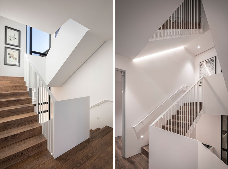 Connecting all of the floors throughout this modern four storey house, is a bright white staircase with wood stairs and hidden lighting. #WhiteStaircase #WoodStairs #StairLighting