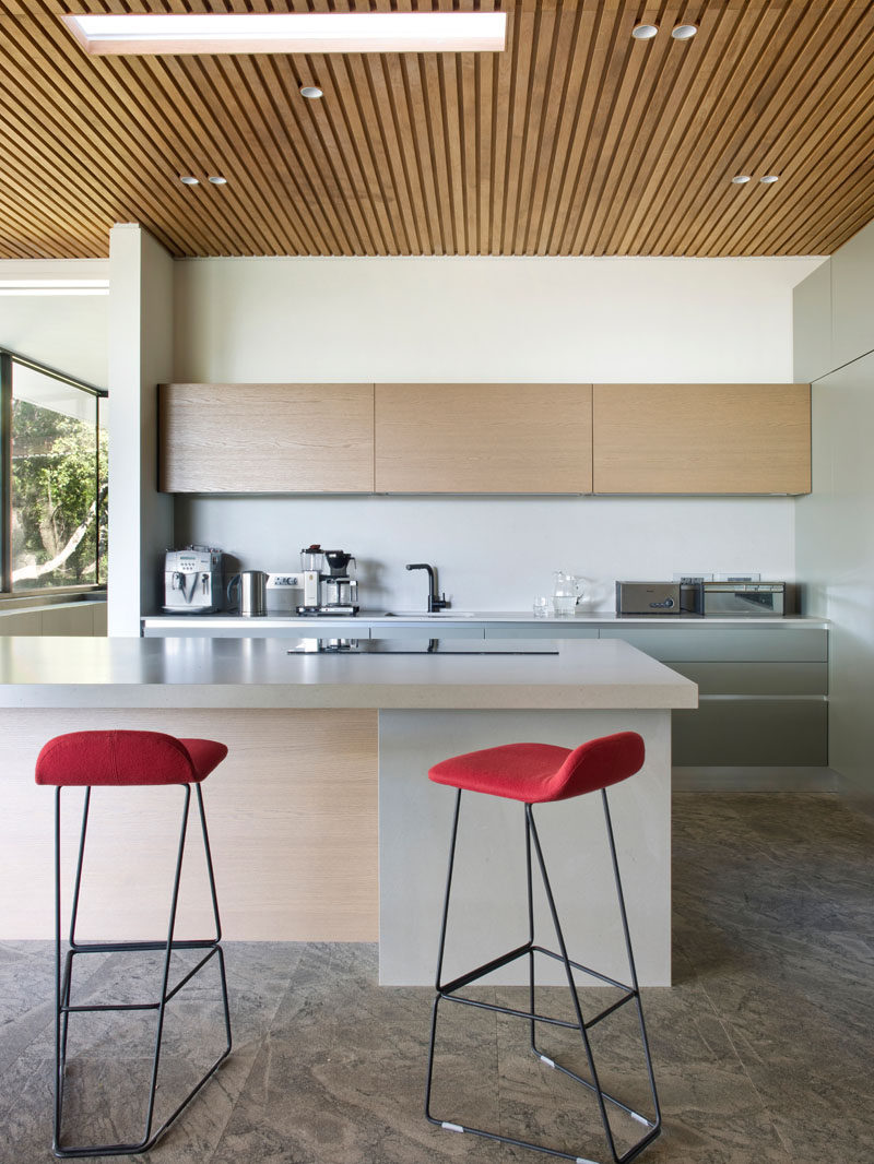 In this modern kitchen, a wood slat ceiling helps to define the space, while Etch bar stools in clementine orange add a pop of color to the mostly neutral palette. #ModernKitchen #KitchenDesign