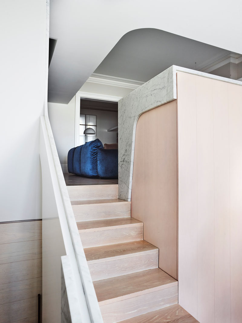 In this house renovation, wood steps lead from the formal living room down to a new, open and airy living space. #WoodStairs