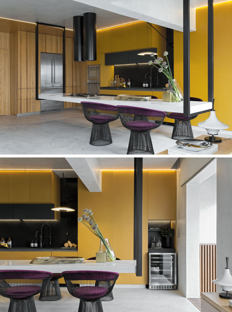 This modern kitchen features an eye-catching hanging island, that measures in at 14 feet (4.5m) long, and is suspended at its ends by black metal supports. #HangingIsland #KitchenDesign #ModernKitchen