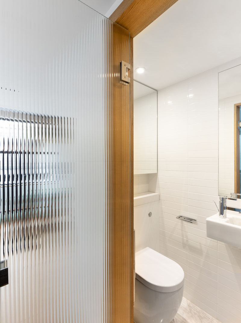This small modern bathroom has white tiled walls, while a textured glass door allows natural light to pass through to the interior. #SmallBathroom #BathroomDesign