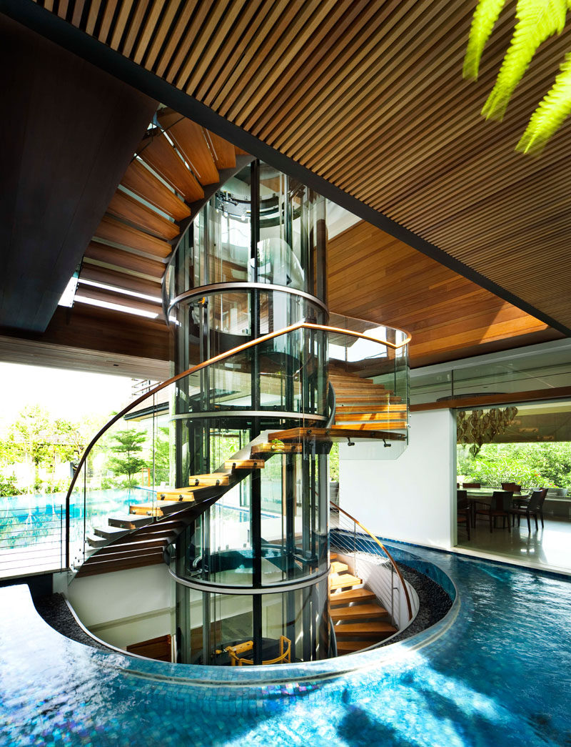 Stairs made from glass, steel, and wood, have been designed as a sculptural element in this modern house, while a wood slat ceiling and the water detail add a natural touch. #Stairs #StairDesign #WaterFeature