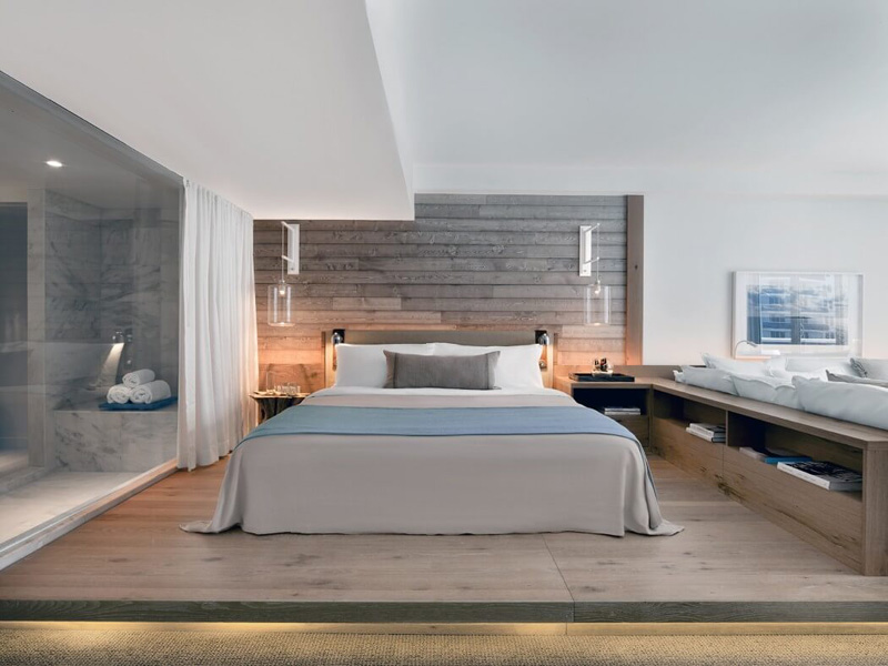 BEDROOM IDEAS - This modern bedroom has a raised sleeping area with hidden lighting, and a wood accent wall behind the bed to match the wood floor. #BedroomIdeas #MasterBedroomIdeas #BedroomDesignIdeas