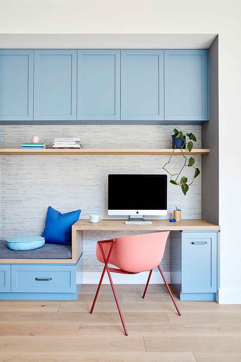 In this modern kitchen, matte light blue cabinets line the wall and transform into a small built-in home office with a bench, while a large white kitchen island provides additional seating. #LightBlueKitchen #ColorfulKitchen #KitchenIdeas #HomeOffice