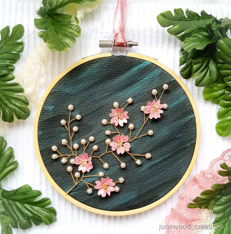 Junewood Creations has crafted a cherry blossom wall hanging that features hand-spun golden wire sprigs adorned with blush pearls and handmade/hand-painted cherry blossoms. #CherryBlossomWallArt #CherryBlossom #CherryBlossomDecor #CherryBlossomArt