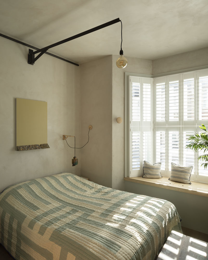This master bedroom has built-in window seat. A large pivoting light hangs above the bed, while smaller pivoting lights have been created as beside lamps. #MasterBedroom #WindowSeat #PivotingPendantLight