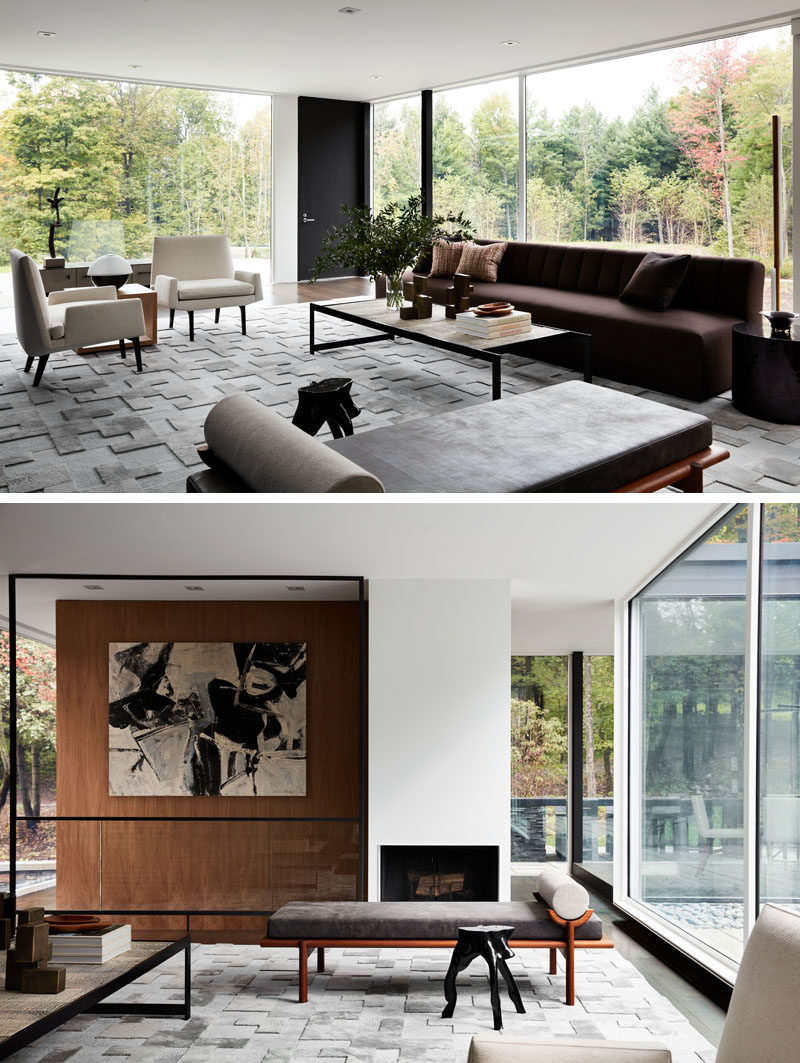 In this modern living room with glass walls, a variety of seating options are arranged to take advantage of the different views on offer. #LivingRoom #ModernInterior #Fireplace