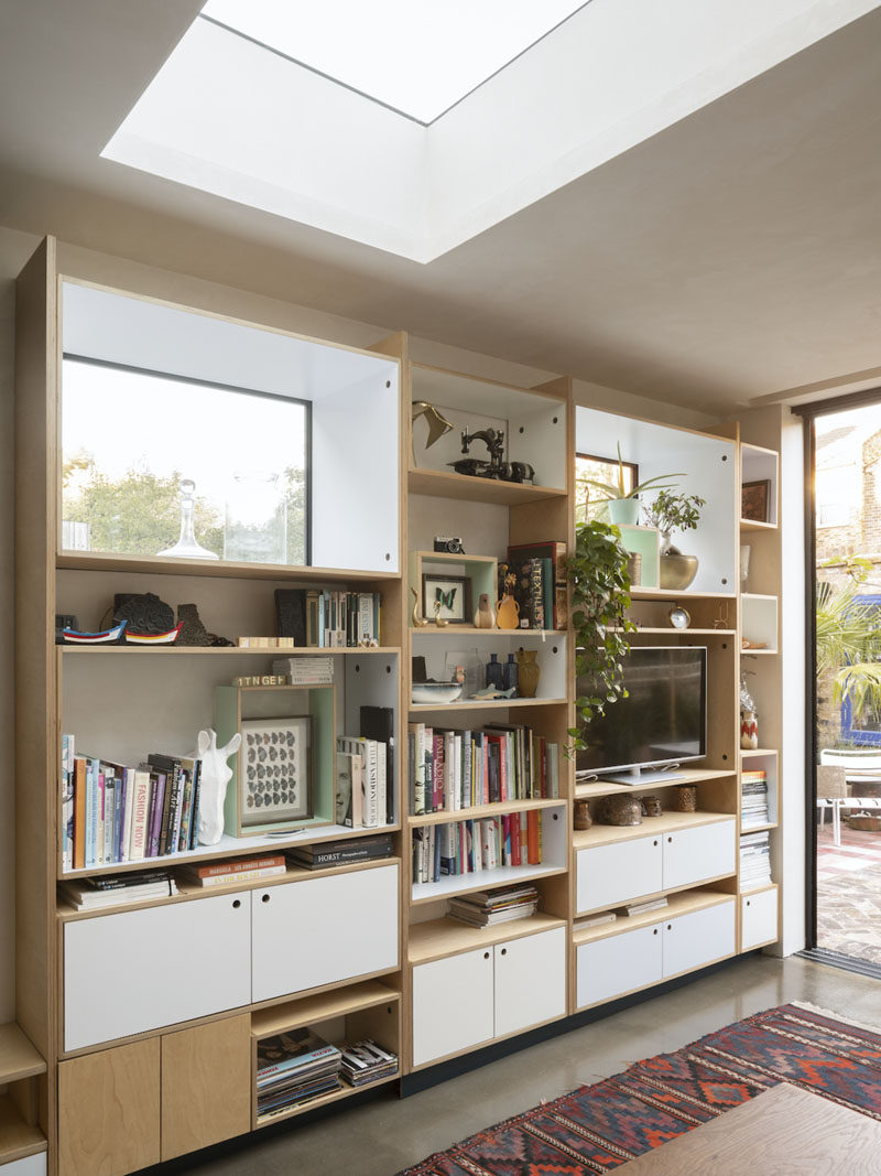 Birch plywood has been utilized for the custom shelving unit in this living room. The shelving provides ample storage, and frames both the television and the window. A skylight helps to keep the space bright. #Shelving #LivingRoom #Windows