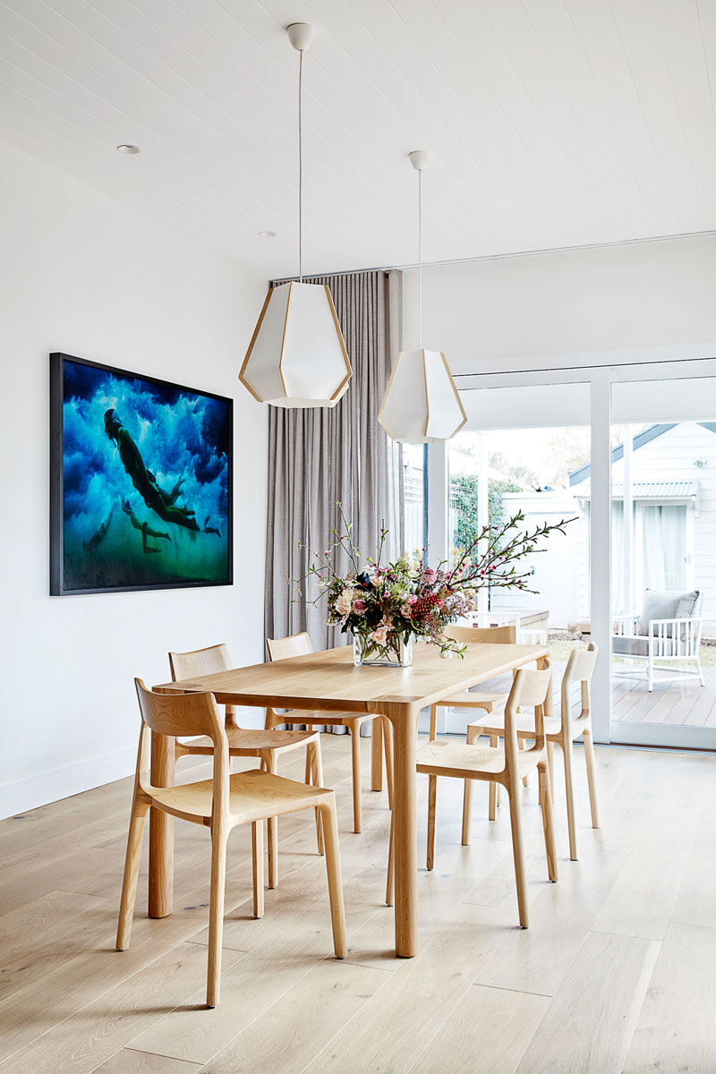 In this modern dining room, two geometric pendant lights hang above a wood dining table and its chairs, while art adds color to the white walls and ceiling. #DiningRoom #ModernDiningRoom #DiningRoomIdeas