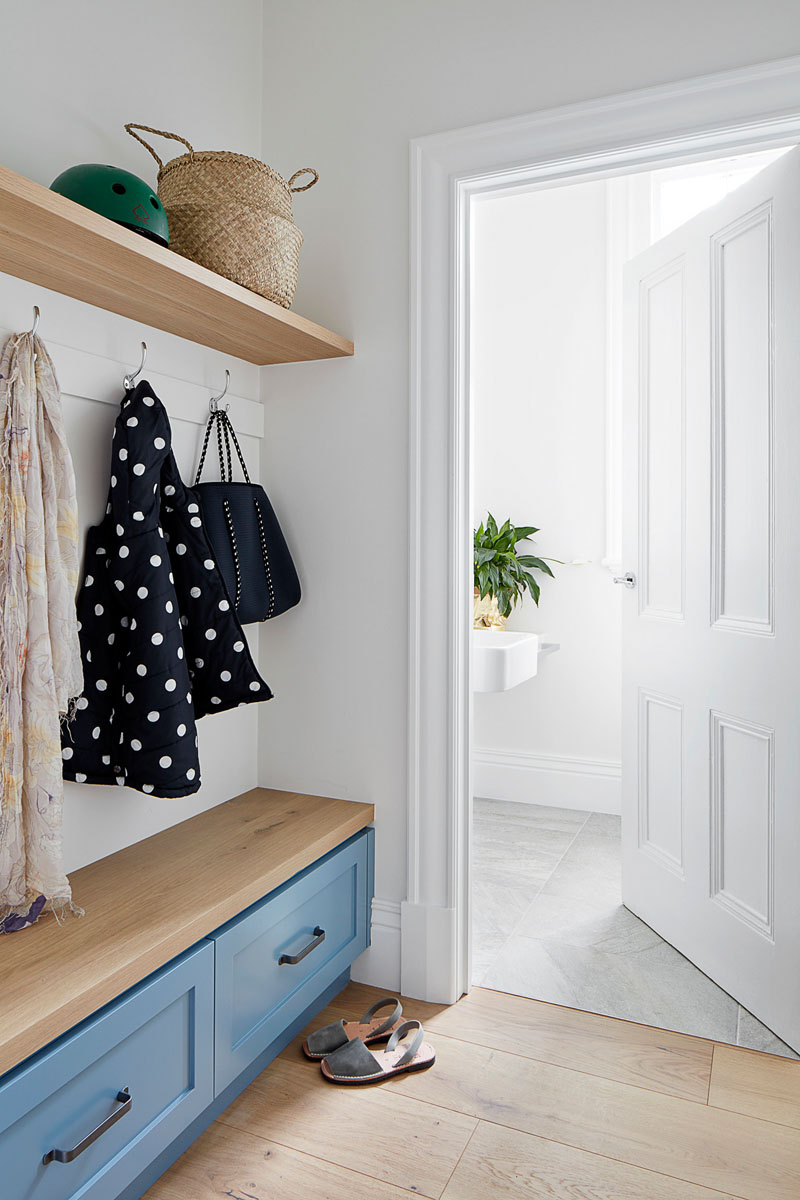 A combination of old and new is featured throughout this updated house, like in the entryway, where new built-in cabinetry and wood shelving has been added, while the door designs and trim work reference the original elements of the home. #Entryway #PowderRoom #InteriorDesign