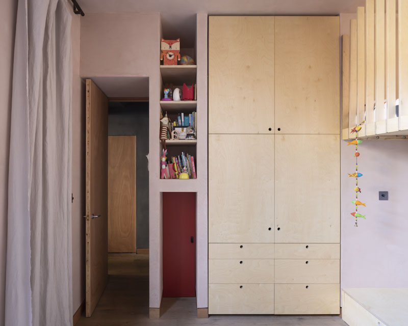 In this modern kids bedroom, a red mini-door allows the children a fun and unique way to enter their room, while built-in shelving and closets provide much needed storage. #KidsBedroom #Storage #Shelving