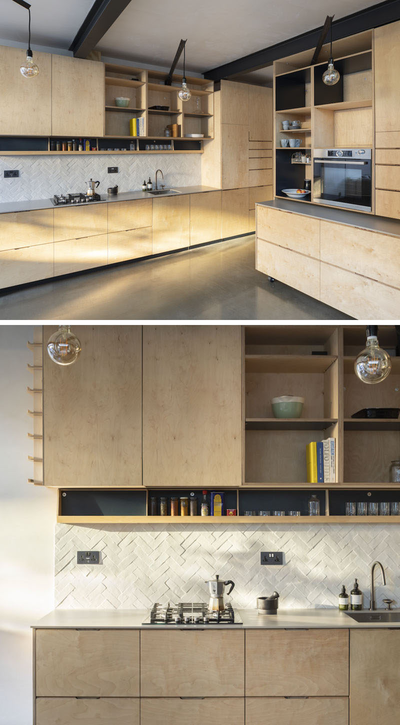 In this wood kitchen, birch plywood has been used for the cabinets, while a movable island on industrial casters, slots under the area where the oven is located, allowing the family to create a large open space for entertaining. #WoodKitchen #PlywoodKitchen #KitchenDesign