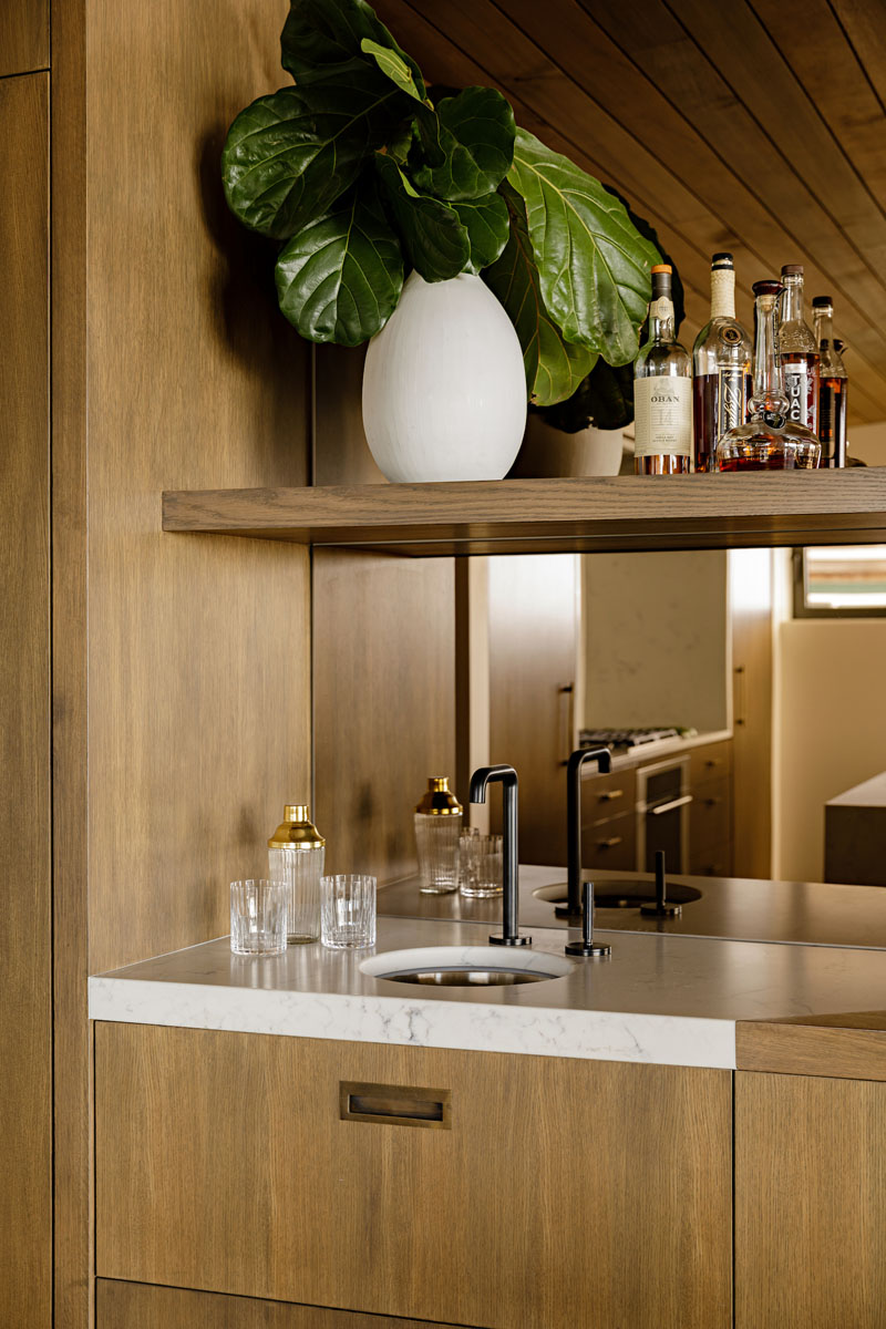 This modern bar has a mirrored backsplash that reflects the kitchen. #MirroredBacksplash #HomeBar #Bar