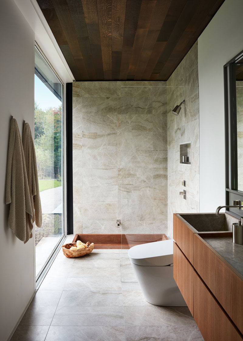 In this modern bathroom, a glass shower screen almost appears invisible, and the bath has been sunken down into the floor beside the shower, both of which have a view of the trees outside. #ModernBathroom #BathroomDesign #SunkenBathtub