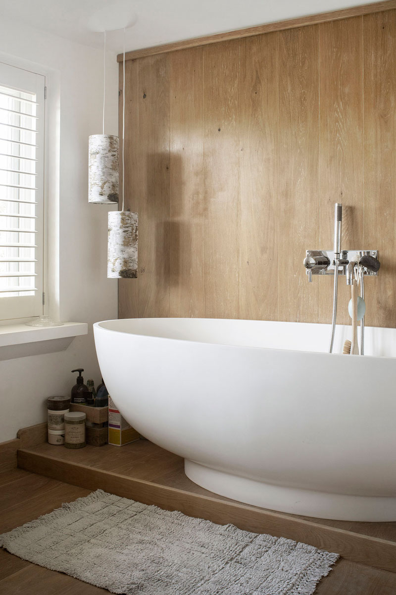In this modern bathroom, a wood covered wall becomes the backdrop for the freestanding bathtub, while the window provides natural light. #ModernBathroom #WoodWall #BathroomDesignIdea