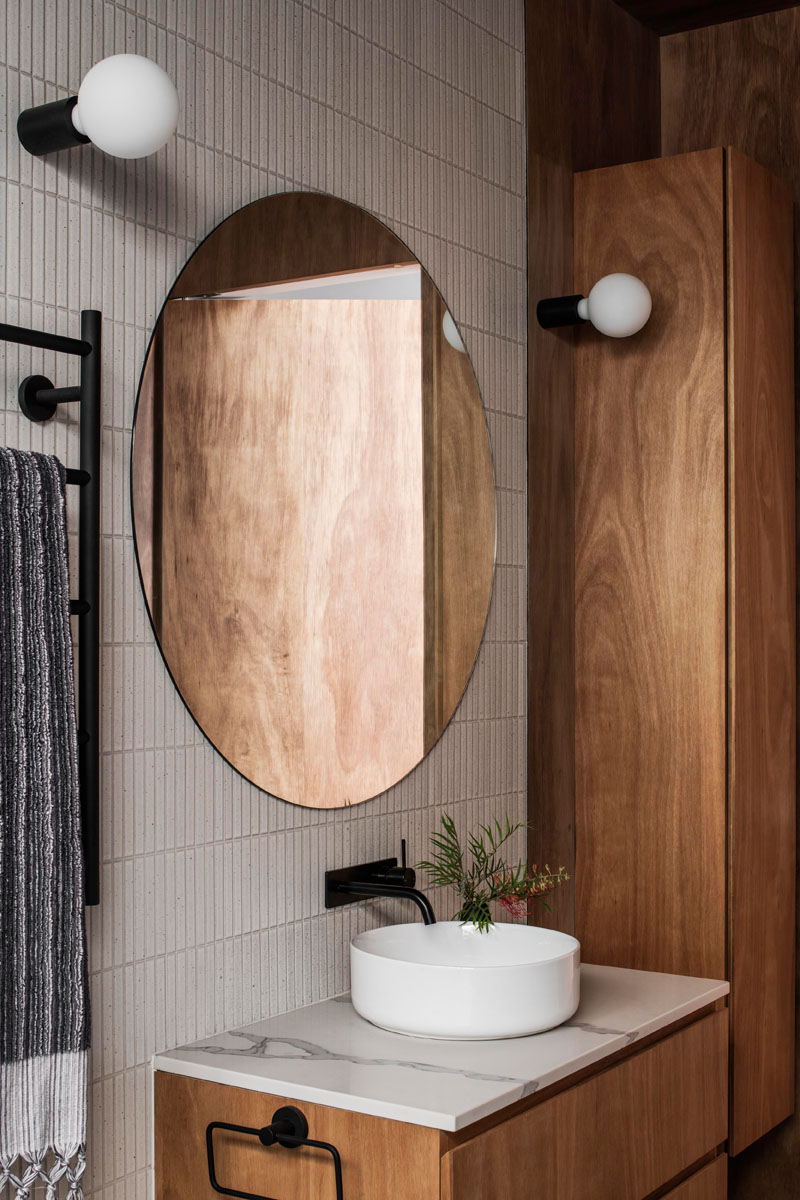 This modern bathroom features tile covered walls, a wood vanity and matching cabinetry, and a round mirror with sconces either side. #ModernBathroom #RoundMirror #WoodVanity #Sconces #TiledWall
