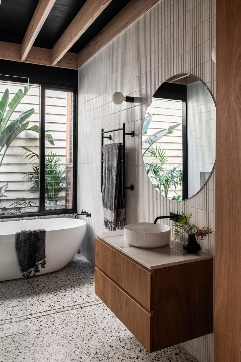 In the bathroom, tiles cover the walls, while a freestanding bathtub is positioned beneath the window, and a minimalist glass shower screen allows the natural light from the window to filter throughout the room. #ModernBathroom #BathroomDesign #TiledWalls #RoundMirror