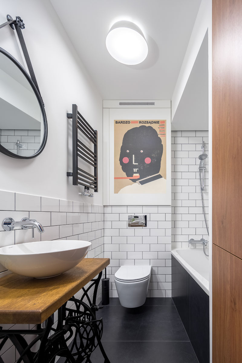 This modern bathroom features large black tiles on the floor, a show/bath combo, white subway tiles with dark grout, a hanging round mirror, and a custom vanity whose stand is made from the base of an old sewing machine. #ModernBathroom #BlackFloorTiles #WhiteSubwayTiles #BathroomDesign