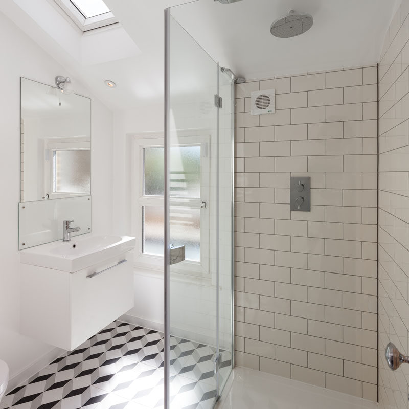 In this modern bathroom, a skylight adds natural light, while on the floor, a geometric tile pattern adds an artistic touch. #ModernBathroom #GraphicTiles #SubwayTiles