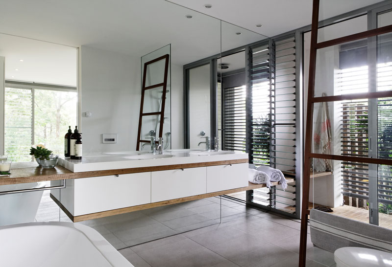 In this bathroom, a wall of mirrors helps to reflect the light from the windows, and also makes the room feel larger. #ModernBathroom #BathroomDesign #BathroomMirror