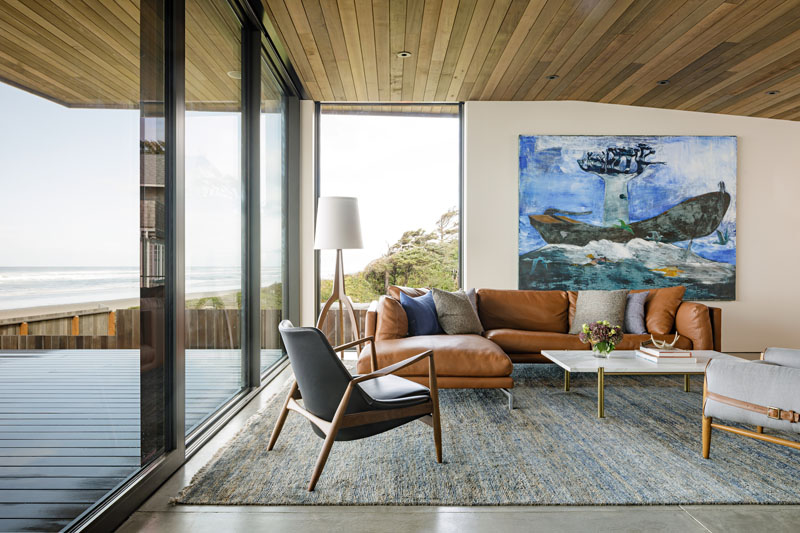 This beachfront living room has polished concrete flooring, a wood ceiling, and modern furnishings, that come together to create a comfortable space to relax. #LivingRoom #WoodCeiling #ConcreteFloor