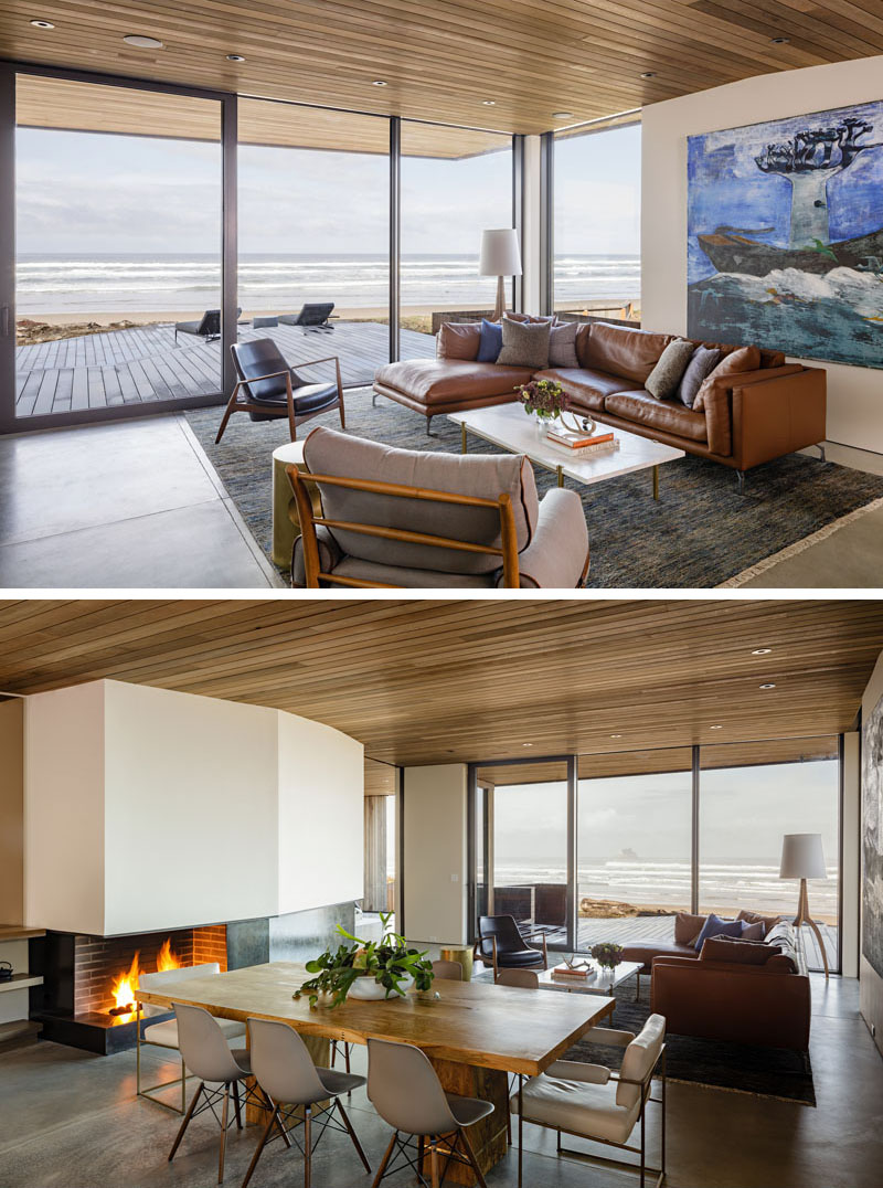 In this modern beachfront living room, floor-to-ceiling windows allow for ample natural light, while a door provides access to a deck, and on a cool night, a fireplace provides warmth. #LivingRoom #DiningRoom #Fireplace #Windows #Deck #WoodCeiling