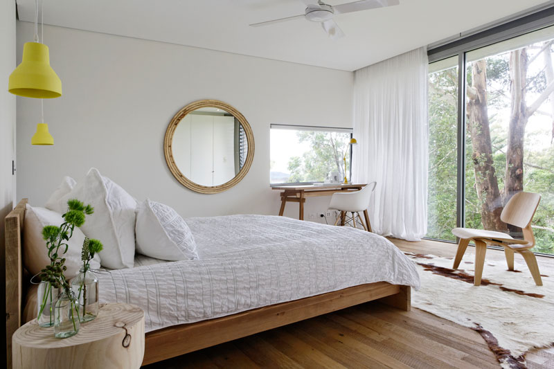 In this modern bedroom, a floor-to-ceiling window frames the trees, while a small work area takes advantage of a window to keep the desktop bright. #ModernBedroom #BedroomDesign