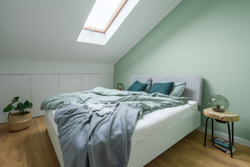 In this modern bedroom, a soft mint green accent wall provides a backdrop for the bed, while a skylight adds natural light to the room, and storage cabinets have been built into the wall. #ModernBedroom #BedroomIdeas #MintGreen