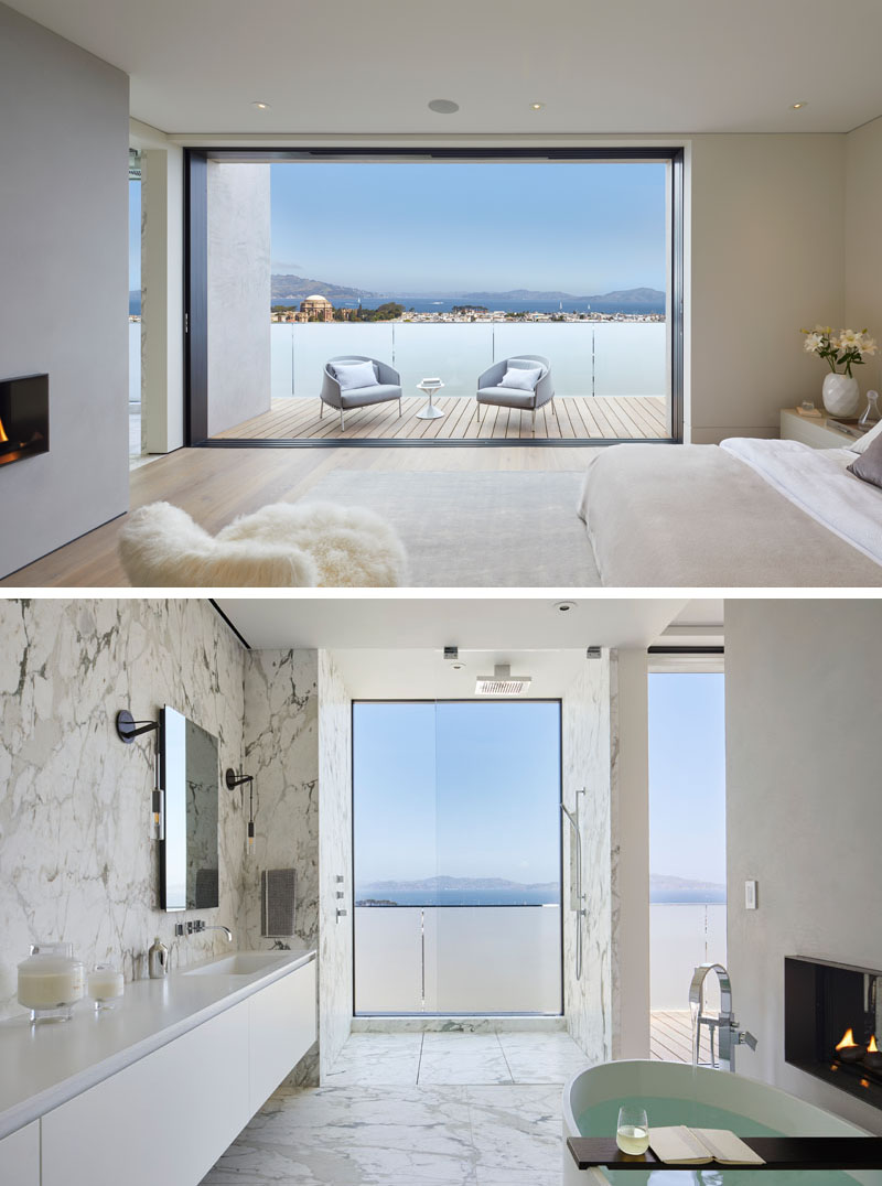 This modern bedroom has sliding doors that open to a balcony with frosted glass, creating privacy for the occupants, while a double-sided fireplace can be enjoyed from both the bedroom and the ensuite bathroom. #ModernBedroom #ModernBathroom #MasterBedroom
