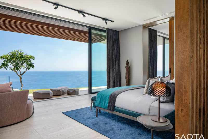 Floor-to-ceiling sliding doors connect this modern bedroom with a small patio, while inside, the blue accents complement the water views. #ModernBedroom #BedroomDesign