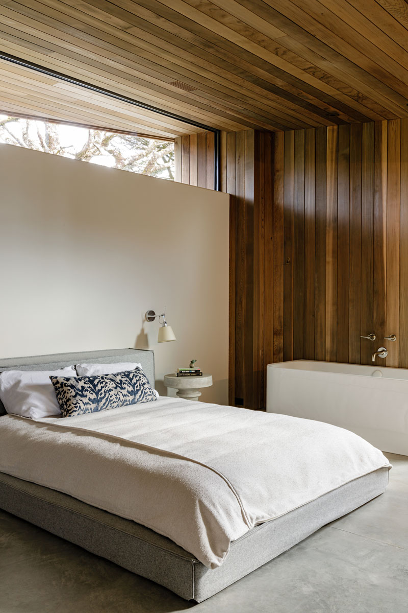 The cedar wood siding used on the exterior of this modern house, continues through to the interior, adding a natural touch and warmth to the bedroom. #WoodSiding #BedroomDesign #WoodWalls #ModernBedroom