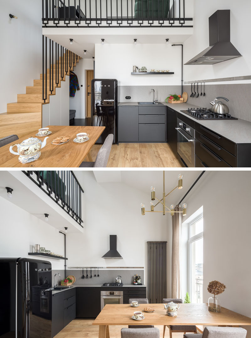 The entryway of this modern apartment opens up to the kitchen and dining area. In the kitchen, matte black cabinets have been combined with a grey countertop and a black fridge for a sleek and modern appearance. #BlackKitchen #ModernApartment #WoodStairs #ModernInterior