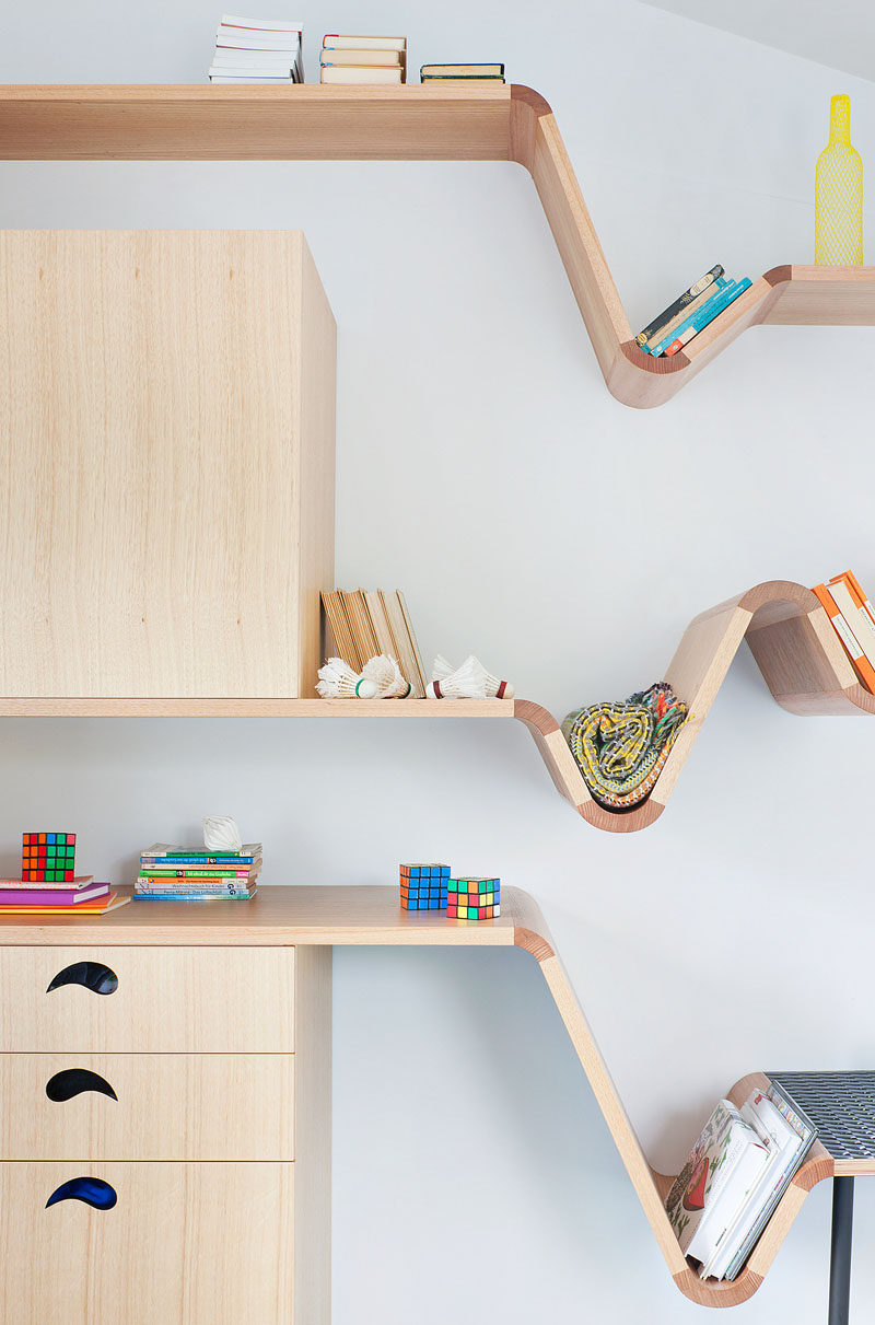 This modern kids bedroom features a custom designed wood desk that transition into benches and shelves. Floating shelving on the walls provides much need additional storage. #Shelving #KidsFurniture #FurnitureDesign