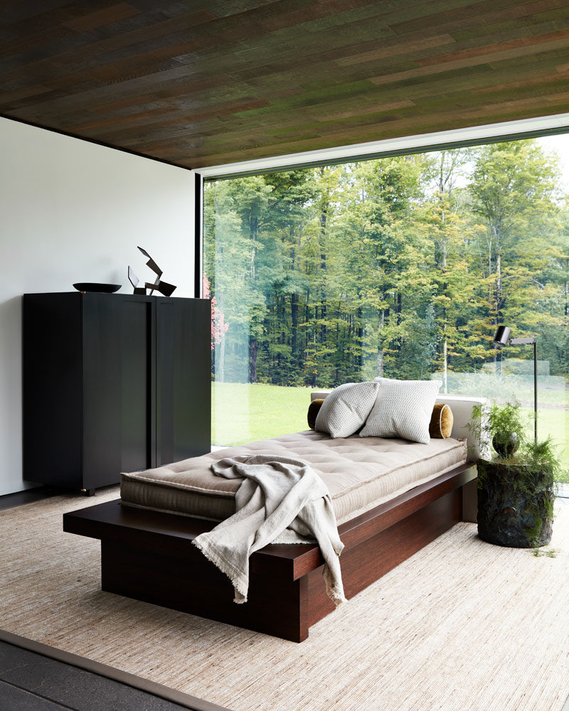 A daybed is centrally positioned in this room with a wood ceiling and glass walls, providing a place for the home owner to relax and enjoy the tree views. #Daybed #InteriorDesign #GlassWalls