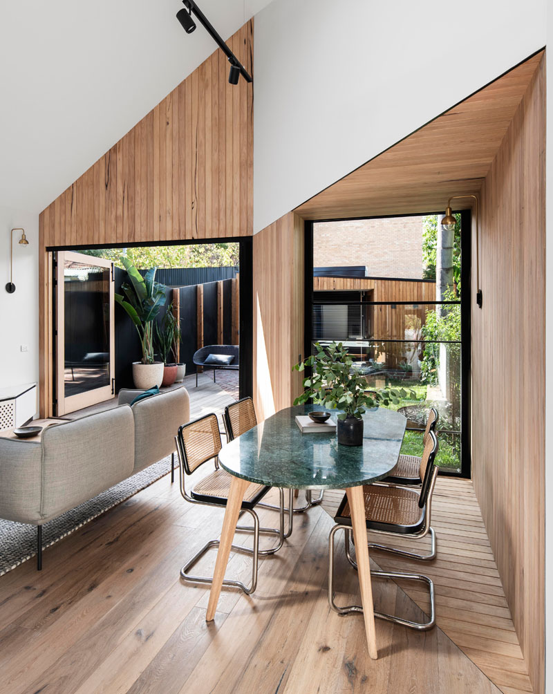 The wood covered walls of this modern house addition highlight the design of the vaulted ceiling, and create a backdrop for the dining table and chairs. #WoodWalls #DiningRoom #VaultedCeiling