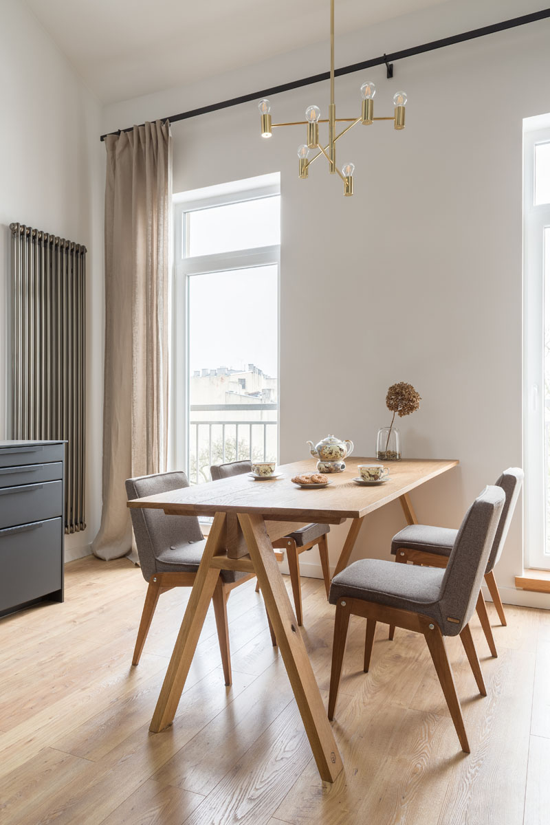 A solid wood oak dinner table is anchored in this apartment by a minimalist chandelier, that draws the eye upwards to showcase the height of the ceiling. #DiningRoom #ModernApartment #InteriorDesign