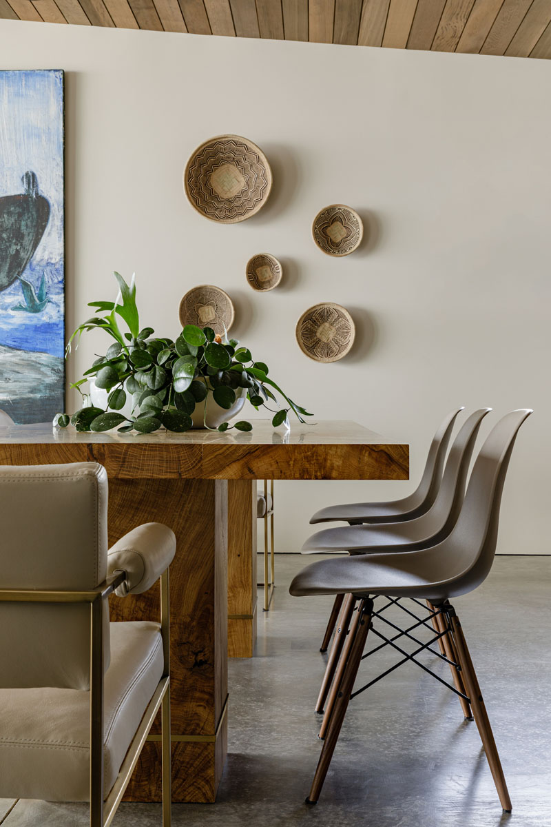 This modern dining room with a large wood table, features a display of mounted baskets on the wall. #DiningRoom #BasketDisplay