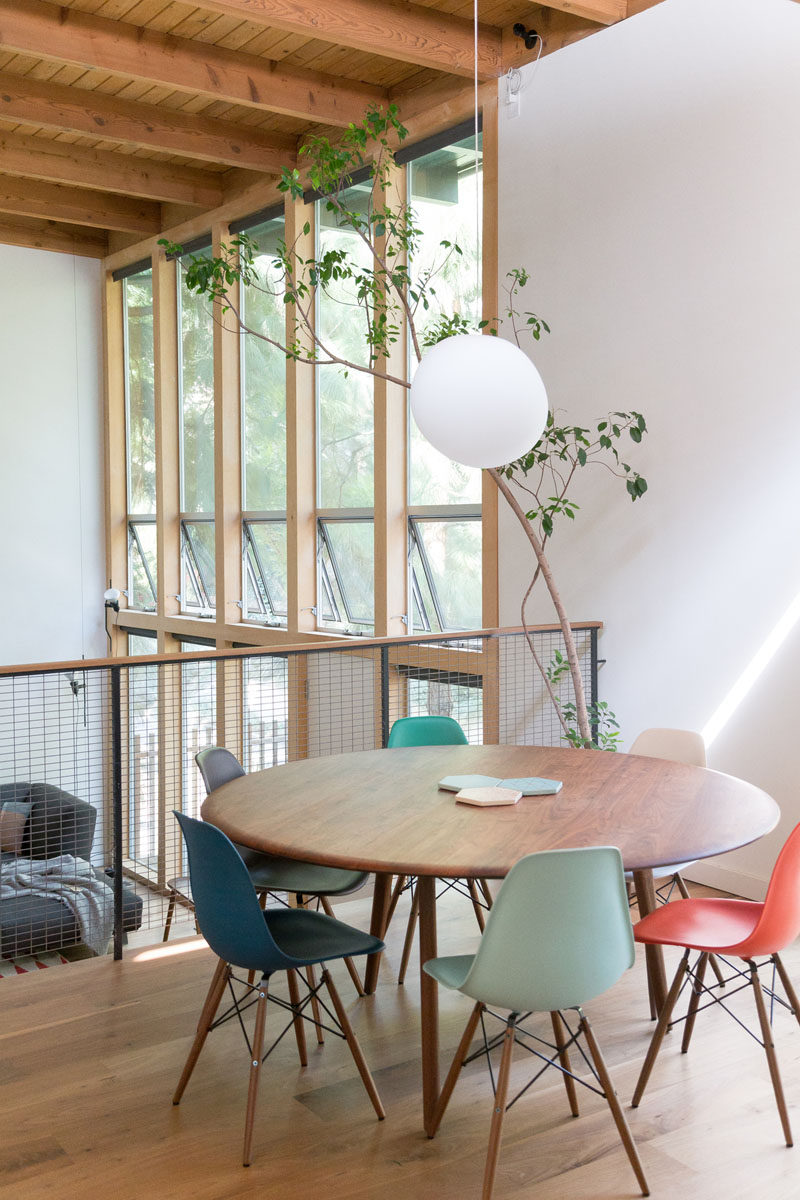 On the split level of this renovated mid century modern house, there's a open dining area with a view of the living room below. A single pendant light helps to define the location of the round dining table. #DiningRoom