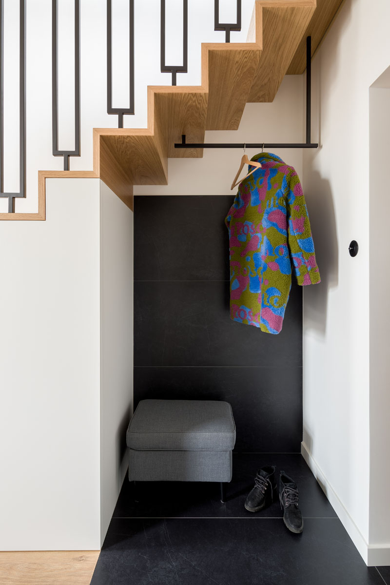 Stepping inside this modern apartment, there's a small entryway with large-scale black tiles that wrap from the floor onto the wall of an alcove underneath the stairs. This alcove provides a place to hang coats and take off shoes, and adjacent to the alcove and underneath the stairs are closets for extra storage. #ModernApartment #Entryway #InteriorDesign