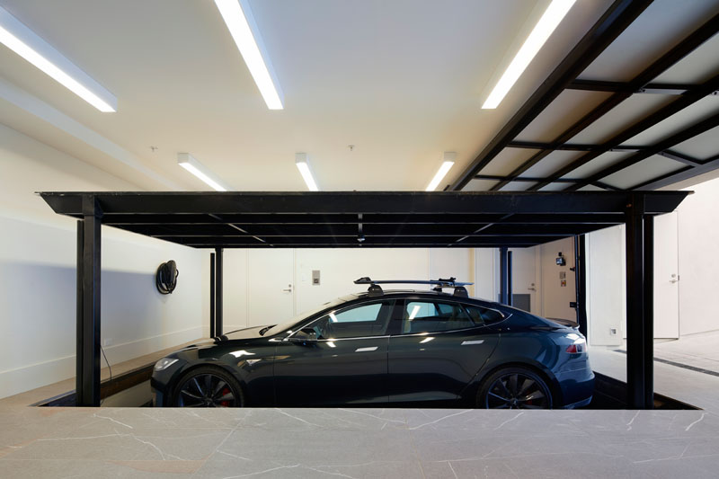This multi-purpose garage boasts a pet spa, a Tesla Power Wall and parking for three cars, including a car vault that allows residents to easily lower a vehicle to the ground floor. #Garage #ModernGarage