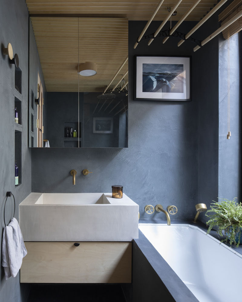 In this modern bathroom, dark grey blue has been used to contrast the wood ceiling. #DarkBlueBathroom #BlueBathroom #ModernBathroom