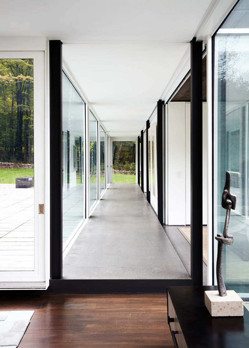 The floor-to-ceiling glass walls throughout this modern house fill the interior with an abundance of natural light. #ModernHouse #GlassWalls #Hallway