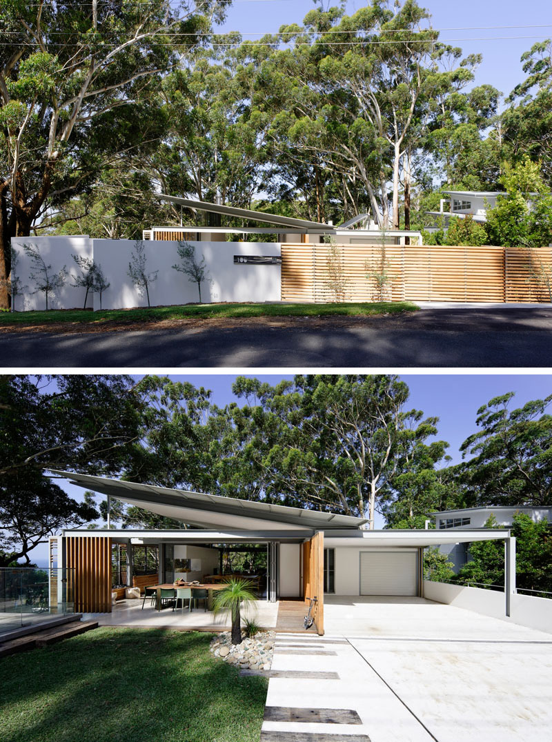 From the street, a wood fence opens to reveals this modern house with an angled roof and an expansive front yard with a covered outdoor dining room. #ModernHouse #HouseDesign #AngledRoof